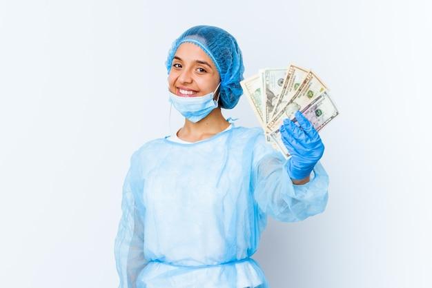Молодая женщина-врач смешанной расы, держащая доллары на белом фоне