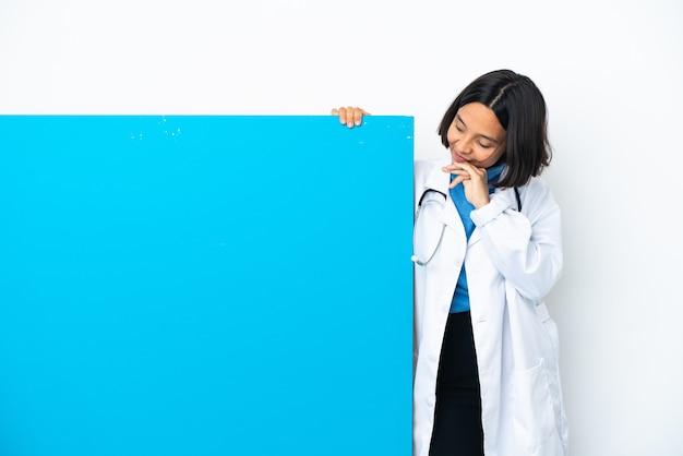 Молодая женщина-врач смешанной расы с большим плакатом, изолированным на белом фоне и смотрящим вверх