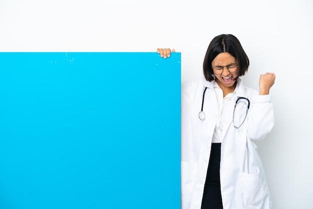 勝利を祝う白い背景で隔離の大きなプラカードを持つ若い混血医師の女性