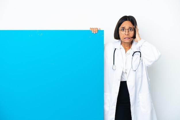 Молодая женщина-врач смешанной расы с большим плакатом на белом фоне делает нервный жест