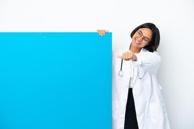 親指を立てるジェスチャーを与える白い背景で隔離の大きなプラカードを持つ若い混血医師の女性