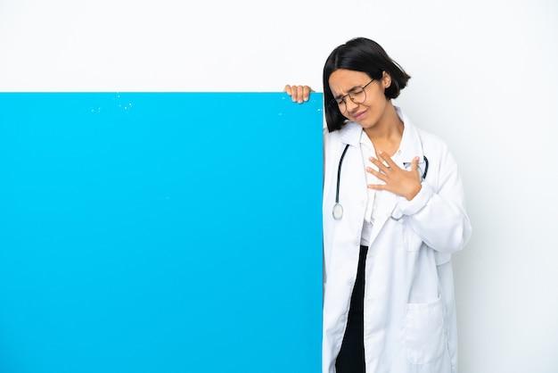 心臓の痛みを持っている白い背景で隔離の大きなプラカードを持つ若い混血医師の女性