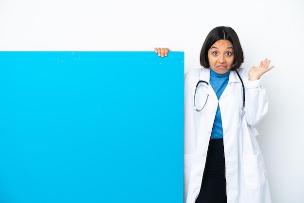手を上げている間疑いを持っている白い背景で隔離の大きなプラカードを持つ若い混血医師の女性