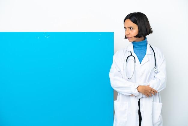 Молодая женщина-врач смешанной расы с большим плакатом на белом фоне, скрестив руки