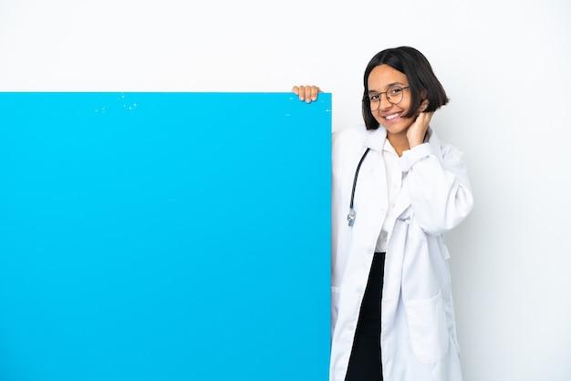 Молодая женщина-врач смешанной расы с большим плакатом на белом фоне смеется