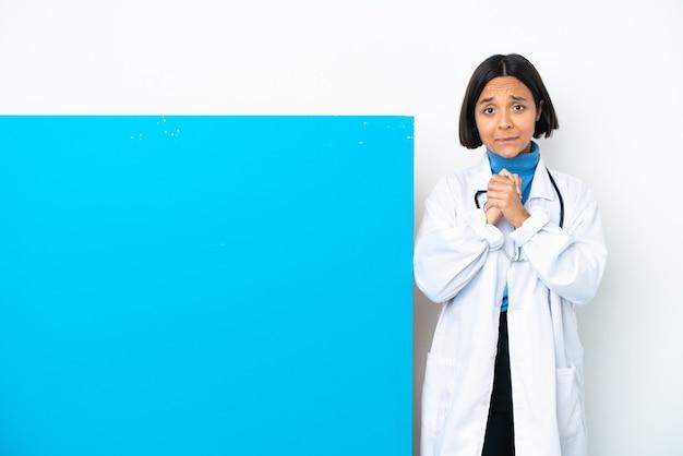 笑って白い背景で隔離の大きなプラカードを持つ若い混血医師の女性