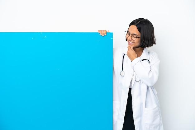 Молодая женщина-врач смешанной расы с большим плакатом на белом фоне смотрит в сторону и улыбается Premium Фотографии