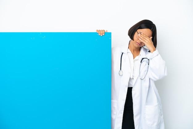 중지 제스처를 만들고 얼굴을 덮고 흰색 배경에 고립 된 큰 현수막을 가진 젊은 혼혈 의사 여자