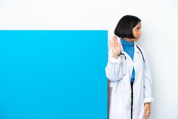 큰 현수막을 가진 젊은 혼혈 의사 여자 중지 제스처를 만드는 흰색 배경에 고립 실망