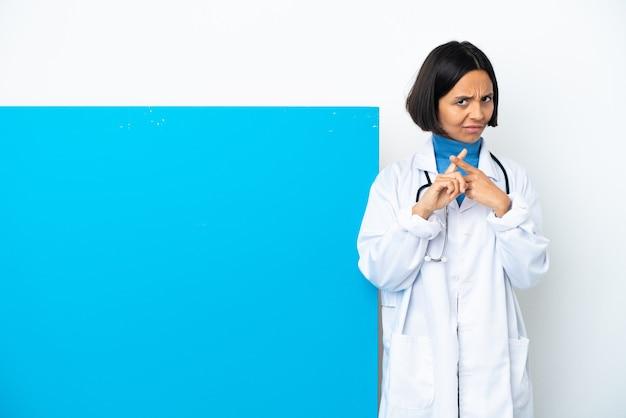 행동을 막기 위해 그녀의 손으로 중지 제스처를 만드는 흰색 배경에 고립 된 큰 현수막을 가진 젊은 혼합 된 인종 의사 여자