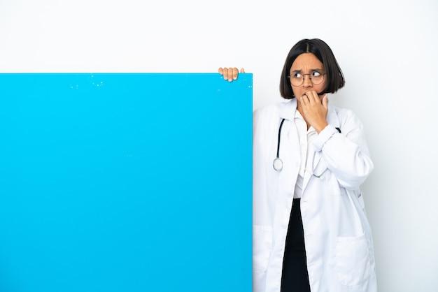 Молодая женщина-врач смешанной расы с большим плакатом, изолированным на белом фоне, нервничала и испугалась, прикладывая руки ко рту