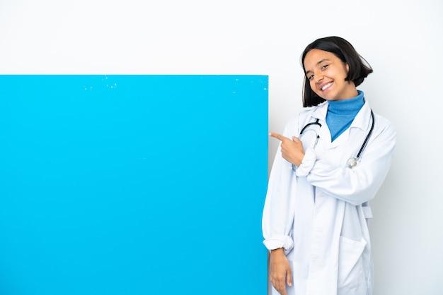 Молодая женщина-врач смешанной расы с большим плакатом на белом фоне, указывающим назад