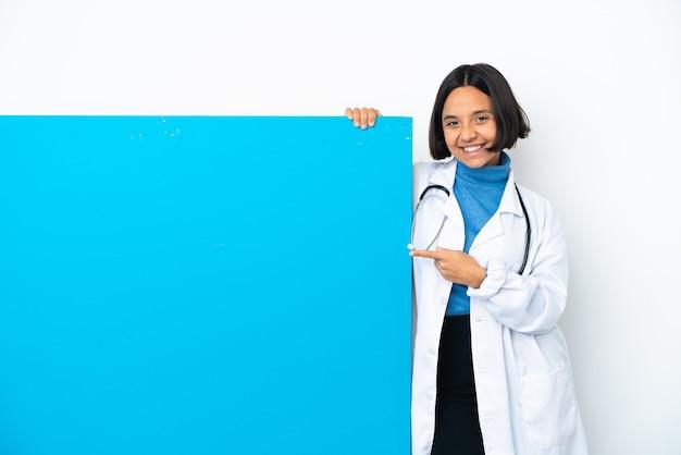 横に指を指している白い背景に分離された大きなプラカードを持つ若い混血医師の女性
