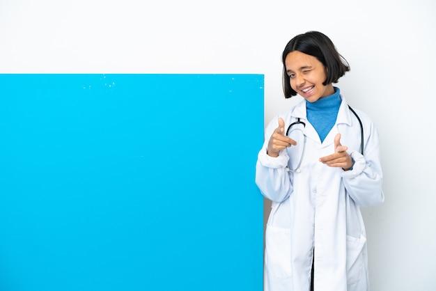 큰 현수막을 가진 젊은 혼합 된 경주 의사 여자는 전면을 가리키고 웃 고 흰색 배경에 고립