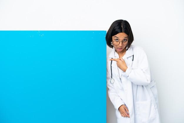 Молодая женщина-врач смешанной расы с большим плакатом, изолированным на белом фоне, указывая в сторону, чтобы представить продукт, и что-то шепчет