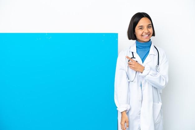 Молодая женщина-врач смешанной расы с большим плакатом на белом фоне, указывающим в сторону, чтобы представить продукт