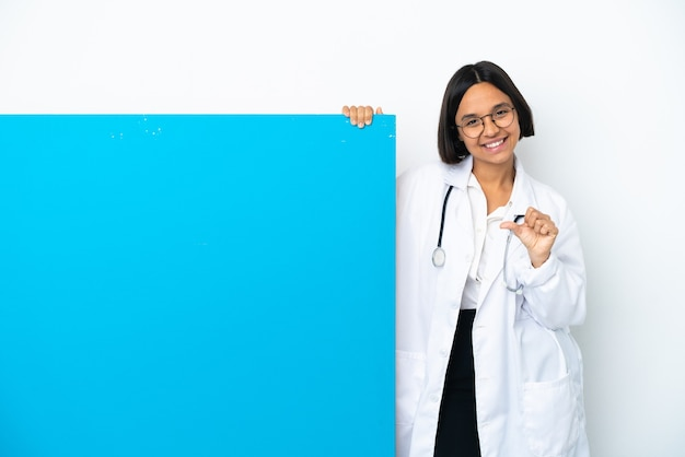 제품을 제시하기 위해 측면을 가리키는 흰색 배경에 고립 된 큰 현수막을 가진 젊은 혼혈 의사 여자