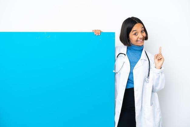 素晴らしいアイデアを指している白い背景で隔離の大きなプラカードを持つ若い混血医師の女性