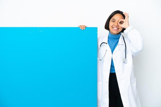Молодая женщина-врач смешанной расы с большим плакатом, изолированным на белом фоне, показывает пальцами знак ок