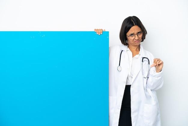두 손으로 엄지손가락을 아래로 보여주는 흰색 배경에 고립 된 큰 현수막을 가진 젊은 혼혈 의사 여자