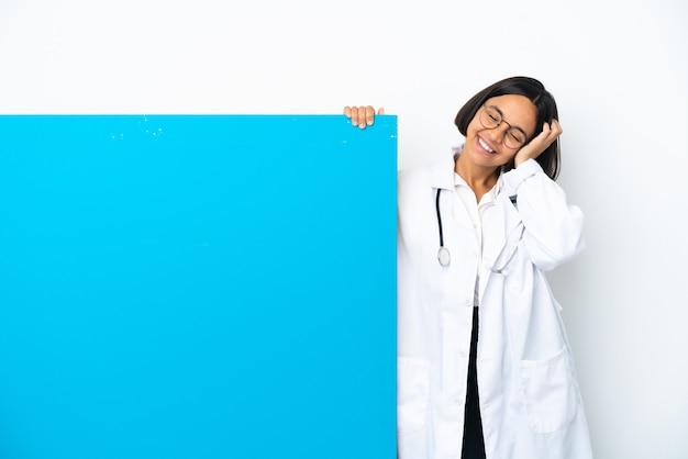 たくさん笑って白い背景で隔離の大きなプラカードを持つ若い混血医師の女性