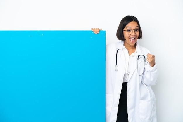 Молодая женщина-врач смешанной расы с большим плакатом на белом фоне удивлена и указывает вперед