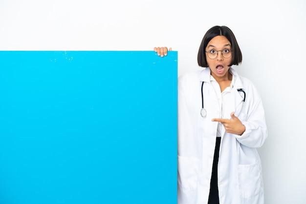 白い背景で隔離の大きなプラカードを持つ若い混血医師の女性は驚いて、側を指しています