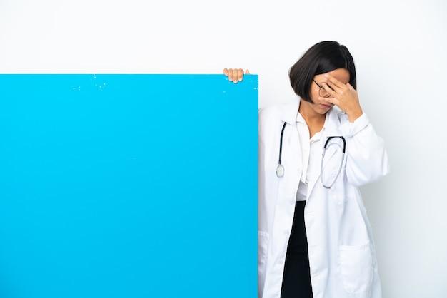 Молодая женщина-врач смешанной расы с большим плакатом, изолированным на белом фоне с головной болью
