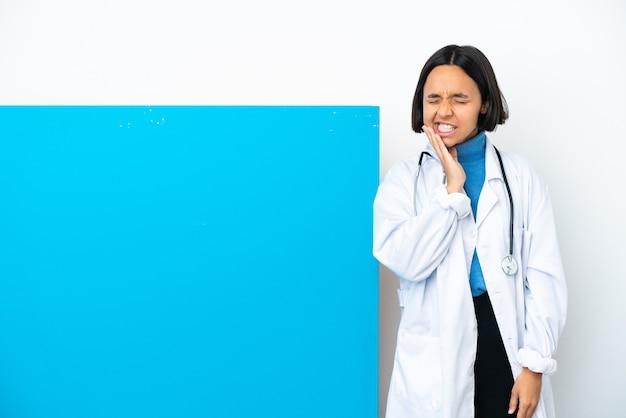 치통과 흰 벽에 고립 된 큰 현수막을 가진 젊은 혼혈 의사 여자