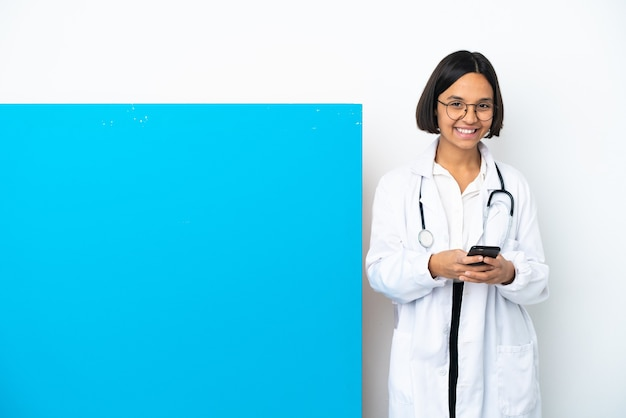 Young mixed race doctor woman with a big placard isolated sending a message with the mobile