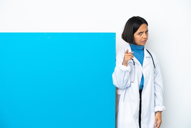 Young mixed race doctor woman with a big placard isolated on white background frustrated and pointing to the front