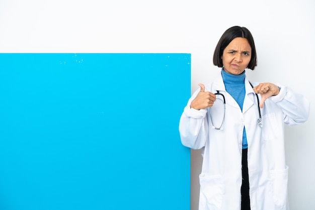 Young mixed race doctor woman with a big placard isolated on white background making good-bad sign. undecided between yes or not