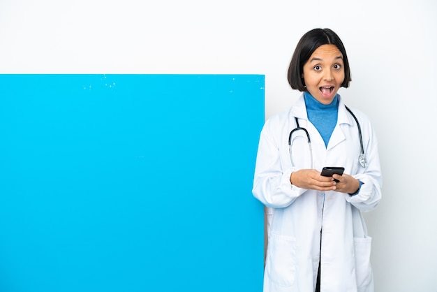 Young mixed race doctor woman with a big placard isolated on white background surprised and sending a message