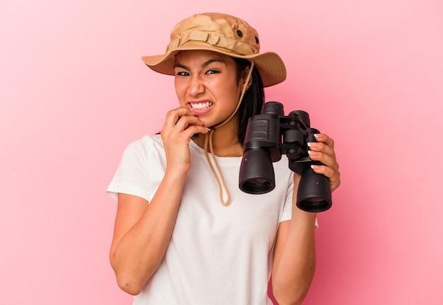 쌍안경을 들고 있는 젊은 혼혈 탐험가 여성은 분홍색 배경에 고립되어 손톱을 물어뜯고 긴장하고 매우 불안해합니다.