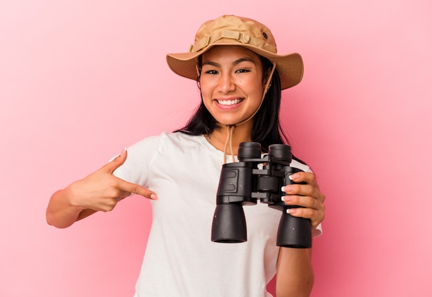 誇りと自信を持って、シャツのコピースペースを手で指しているピンクの背景の人に分離された双眼鏡を保持している若い混血探検家の女性