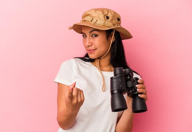 ピンクの背景に分離された双眼鏡を持っている若い混血探検家の女性は、招待が近づくようにあなたに指を指しています。