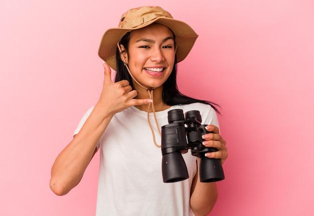 指で携帯電話の呼び出しジェスチャーを示すピンクの背景に分離された双眼鏡を保持している若い混血探検家の女性。