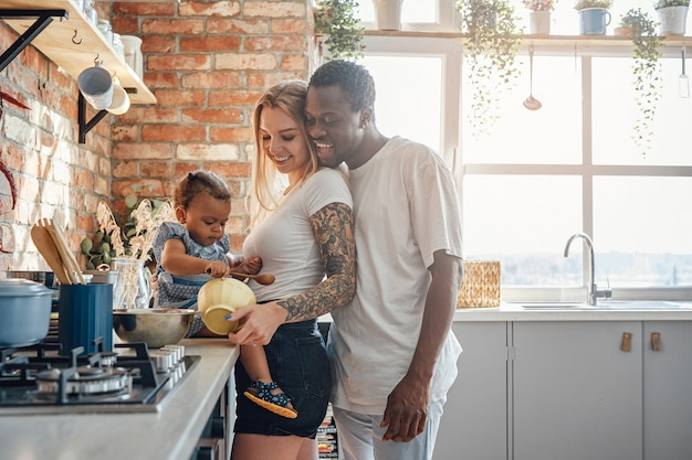 Young mixed race family cooking food on kitchen at home