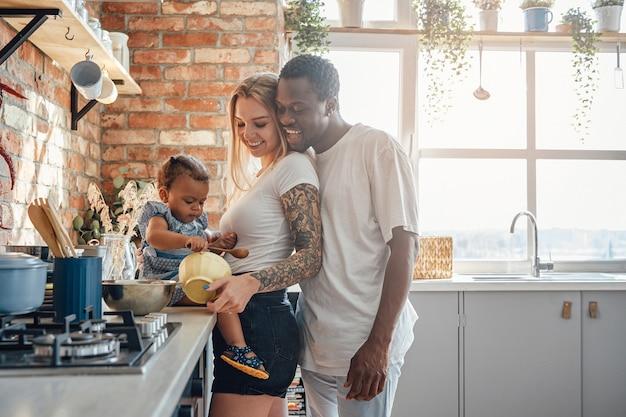 自宅のキッチンで料理をする若い混血家族