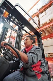 Молодая женщина смешанной расы в спецодежде сидит у руля внутри промышленной машины во время работы на складе напротив стеллажей с упакованными товарами
