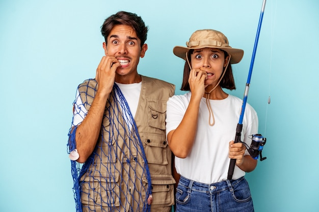 Young mixed race fisher couple isolated on blue background biting fingernails, nervous and very anxious.
