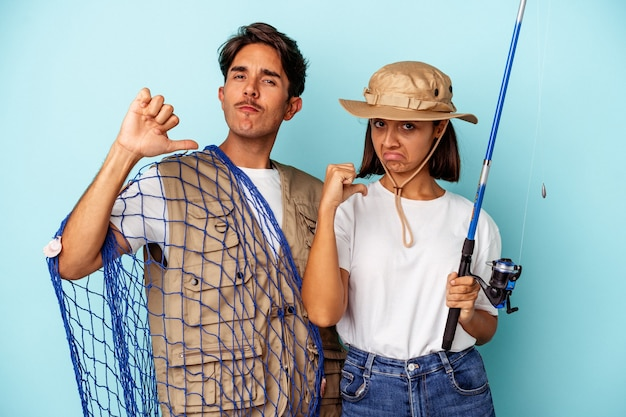 Young mixed race fisher couple isolated on blue background feels proud and self confident, example to follow.