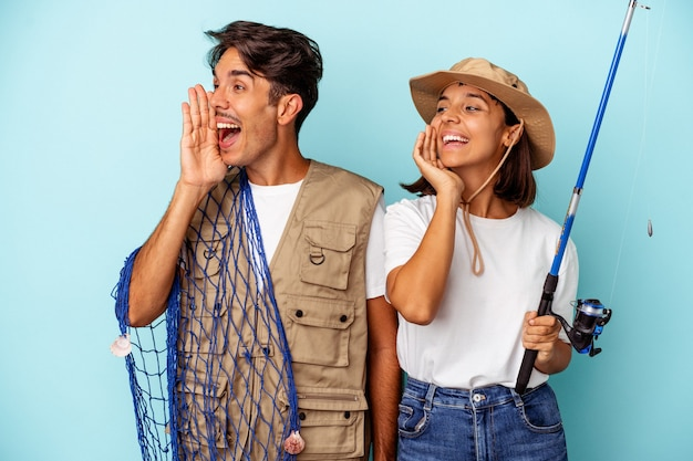 Young mixed race fisher couple isolated on blue background shouting and holding palm near opened mouth.