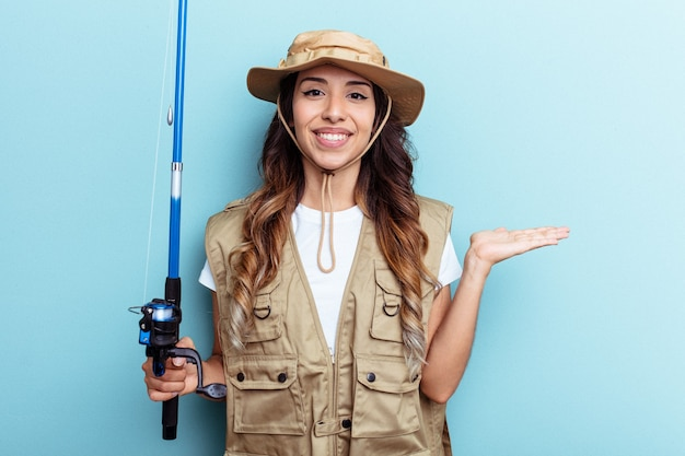 Young mixed race fisherwoman holding a rod isolated on blue background showing a copy space on a palm and holding another hand on waist.
