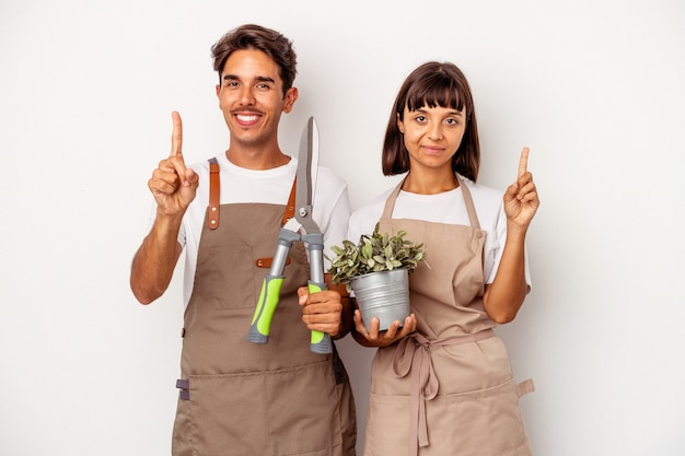 Young mixed race gardener couple isolated on white background showing number one with finger.