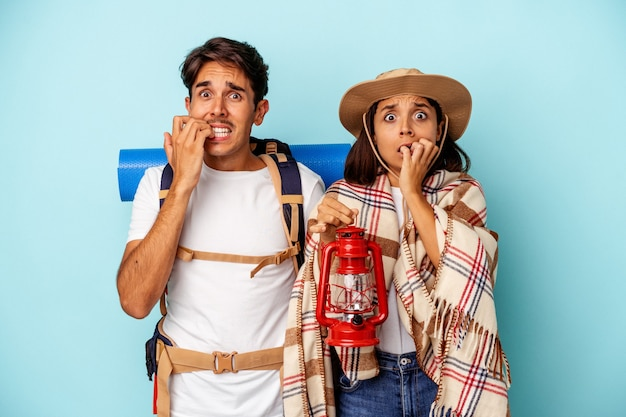 Young mixed race hiker couple isolated on blue background biting fingernails, nervous and very anxious.
