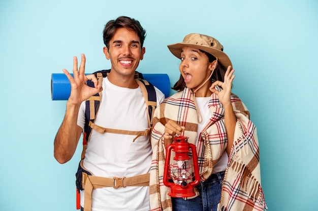 Young mixed race hiker couple isolated on blue background cheerful and confident showing ok gesture.
