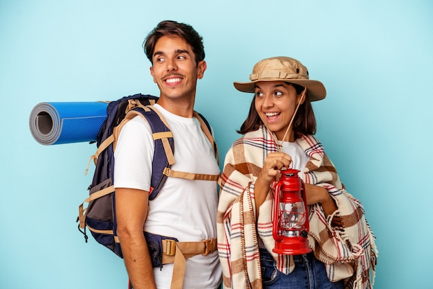 Young mixed race hiker couple isolated on blue background looks aside smiling, cheerful and pleasant.