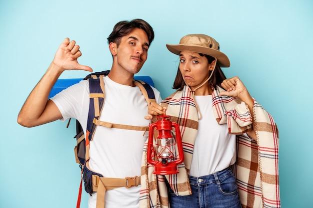 青い背景に隔離された若い混血ハイカーのカップルは、誇りと自信を持って感じています。