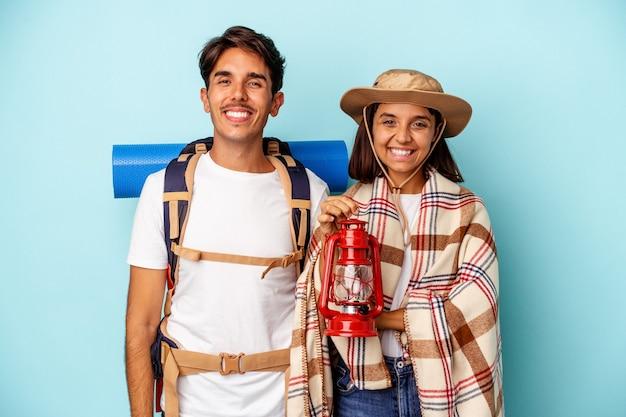 青い背景で隔離の若い混血ハイカーカップル幸せ、笑顔、陽気な。